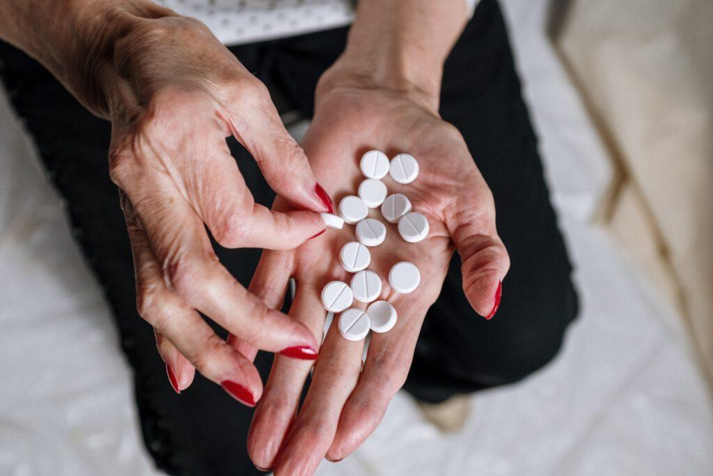 Dłoń z pokazująca dużą ilość tabletek